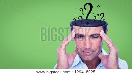 Handsome man thinking with hand on forehead against green background