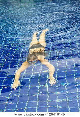 Underwater girlportrait with white bikini in swimming pool.