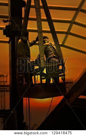 Construction workers standing in the mobile crane bucket over sunset sky