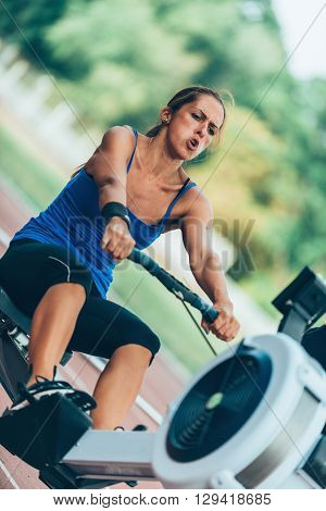 Rowing machine workout, vertical image, selective focus