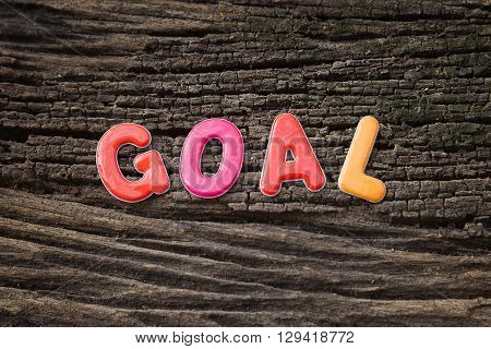 goal word on sticky paper note and paper clip with the old wooden background