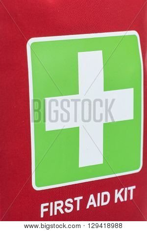 Red First Aid Kit Closeup Background, With Cross Symbol And Text