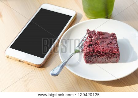 red velvet cake dessert with the phone and drinking with the morning light