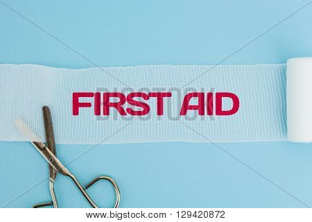 Medical scissors with unrolled gauze with First Aid text, on light blue background.