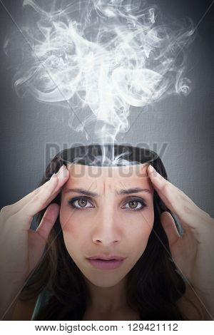 Pretty brunette with a headache against digital image of gray wall