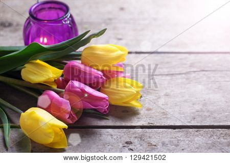 Yellow and pink spring tulips and violet candle in ray od light on aged wooden background. Selective focus. Place for text.