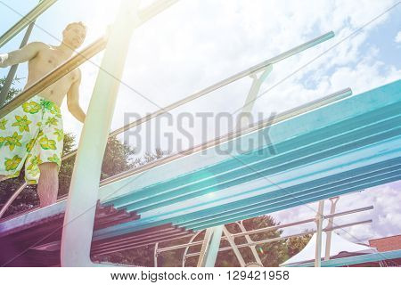 Young man diving off a diving board, with flare from sunlight
