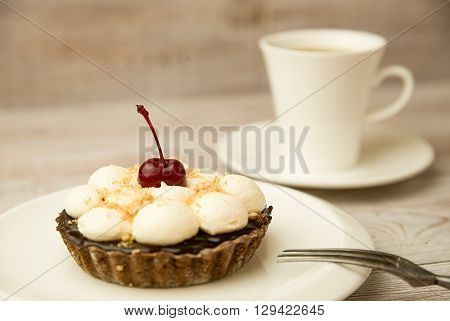 Cake with a cherry and white cup on the table
