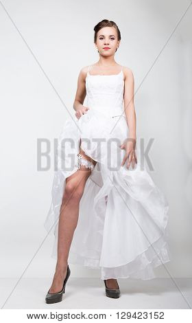 full-length bride in a wedding dress and bridal hairdo, lifted the hem of her dress. provocation playful bride.