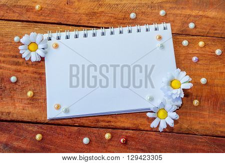 Blank notepad decorated by artificial chamomiles and colorful pearl beads on wooden background