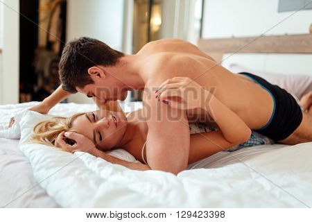 Sensual foreplay by young couple in bedroom