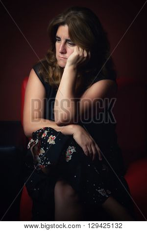 Sad, worried or nostalgic woman sitting lonely in the dark