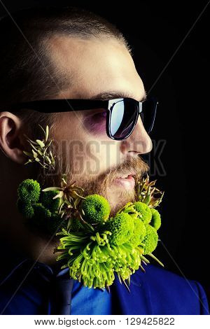 Profile portrait of a handsome man in sunglasses and with a beard of green flowers. Men's beauty. Barbershop.