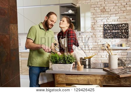 Loving couple cooking together in kitchen, woman kissing man.
