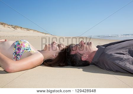 Cute Couple Joining Heads Together On Beach Sand.