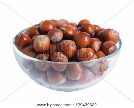 Hazelnuts in a transparent glass bowl isolated on white background.