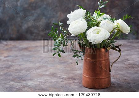 White ranunculus flowers in a cooper vintage jug Brown background Copy space