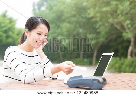 Happy young woman shopping and paying on internet by credit card with laptop computer pc asian beauty