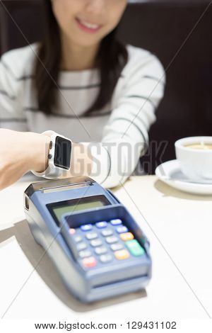 young woman pay by smart watch with empty screen in the restaurant great for your designasian beauty