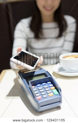 young woman pay by smart phone with empty screen in the restaurant great for your designasian beauty