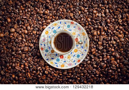 Morning coffee cup with saucer on background with coffee beans top view.