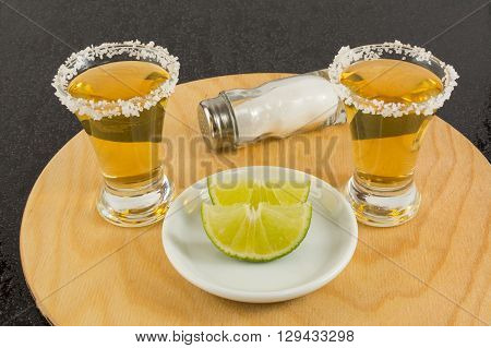 Shots of gold tequila with lime and salt on the wooden tray. Gold Mexican tequila. Tequila. Tequila shot.