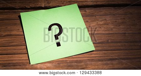 question mark against green paper on wooden floor