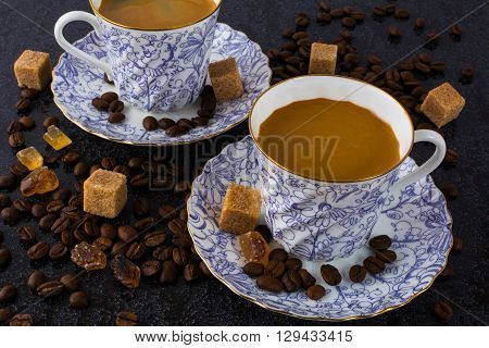 Two coffee cups and coffee beans on black background. Cup of coffee. Coffee cup. Coffee break. Morning coffee