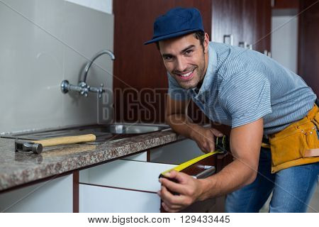 Portrait of smiling man measuring drawer size while bending in kitchen
