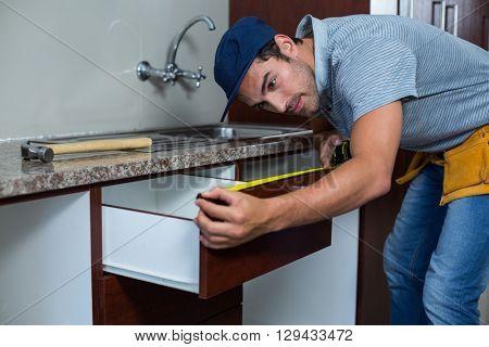 Man measuring drawer size while bending in kitchen