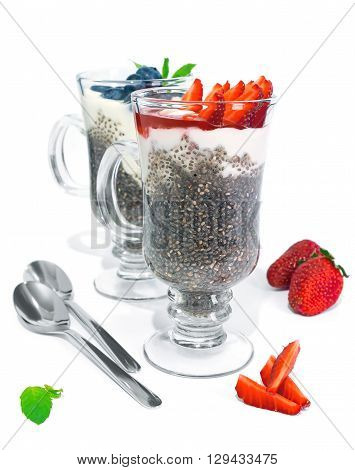 Chia jelly with fresh greek yogurt strawberries and blueberries isolated on white background. Served in glasses with spoons.