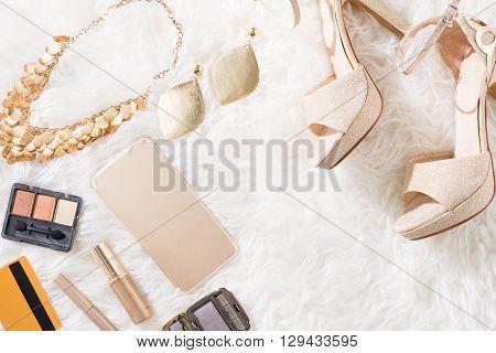 Cosmetics, heels and jewelry on fur bedspread