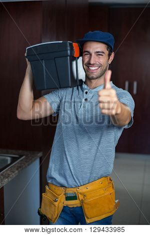 Portrait of smiling man carrying toolbox while showing thumbs up in kitchen