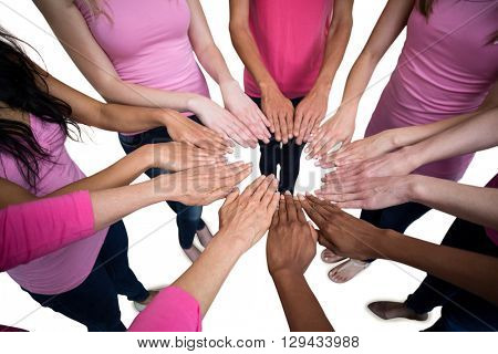Women in pink outfits joining in a circle on white background for breast cancer awareness