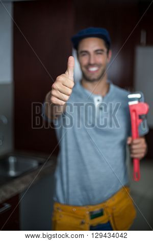 Portrait of cheerful man showing thumbs up while holding pipe wrench in kitchen