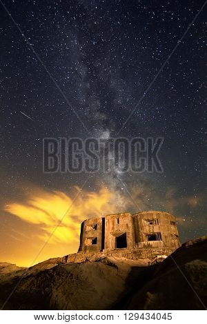The Milky Way shines bright over a bunker on spain coast. Long exposure with light painting.
