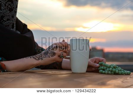 Hand of Middle Eastern Woman with Painted Traditional Tattoo Ornament Coffee Mug and Rosary on Vintage Wood Table Sunrise Sky on Background