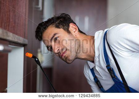 Confident worker using crop sprayer at home