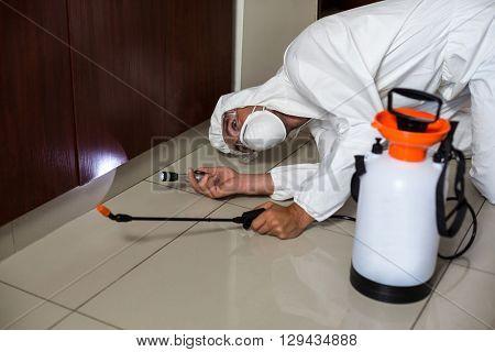 Worker using flashlight under cabinet in kitchen at home