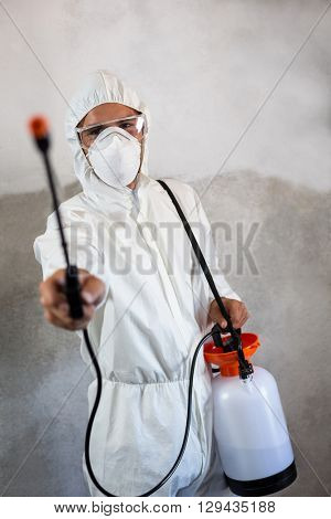Portrait of manual worker holding crop spray against walll