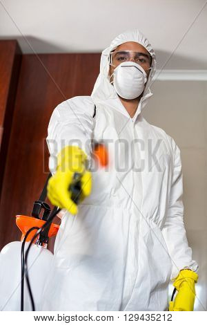 Low angle portrait of manual worker with pest sprayer standing at home