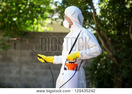 Side view of worker wearing protective suit using pesticide in back yard