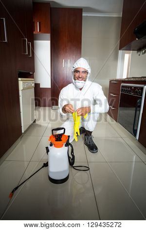 Portrait of manual worker wearing protective gloves while kneeling in kitchen