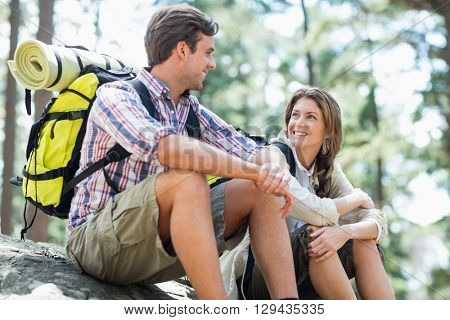 Couple looking face to face while sitting on rock in forest