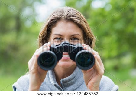 Close-up of smiling woman with binoculars in forest