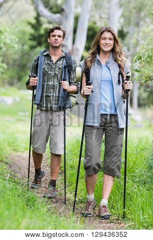 Full length of hikers walking with poles in forest