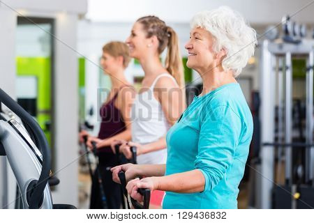 Senior and young people on vibrating plates in gym doing fitness exercise