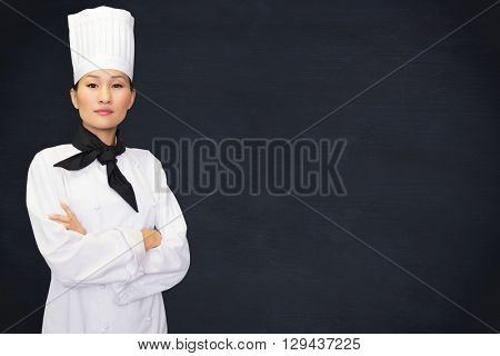 Portrait of confident female cook in kitchen against blackboard