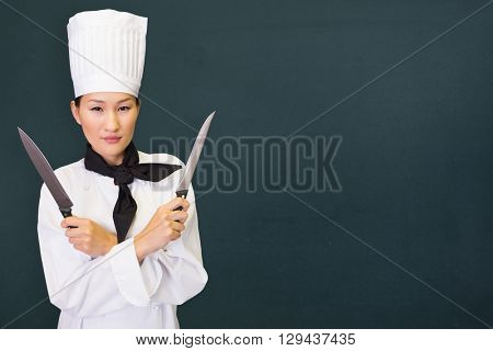 Confident female cook holding knives in kitchen against chalkboard
