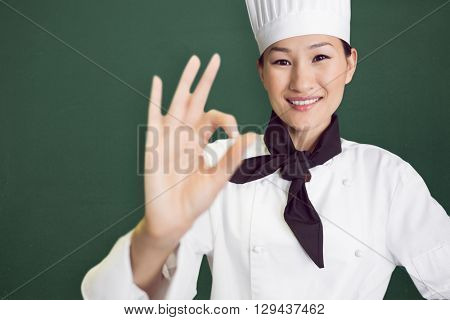 Image of a chalkboard against smiling female cook gesturing okay sign in kitchen
